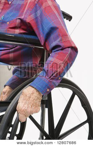Caucasion male elderly hands gripping wheels of wheelchair.