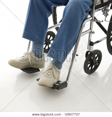 Legs and feet of elderly man sitting in wheelchair.