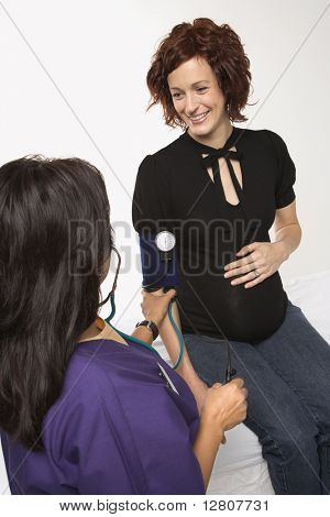 Schwangere kaukasischen adult Woman having Vitalfunktionen von Krankenschwester überprüft.