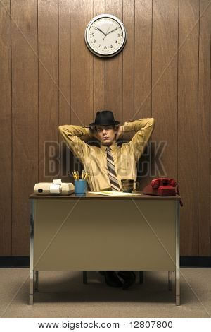 Caucasion mid-adult retro businessman wearing fedora sitting at desk leaning back with hands behind head.