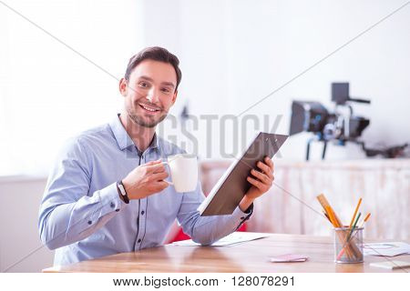 Enticed in joy. Cheerful smiling handsome delighted man sitting at the table and holding folder while drinking coffee