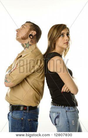 Hombre caucásico de mid-adult y adolescente femenino pie espalda con espalda.