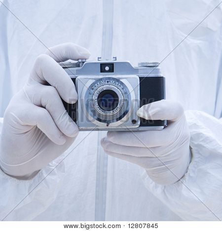 Man in biohazard suit holding antique camera with finger on shutter button.