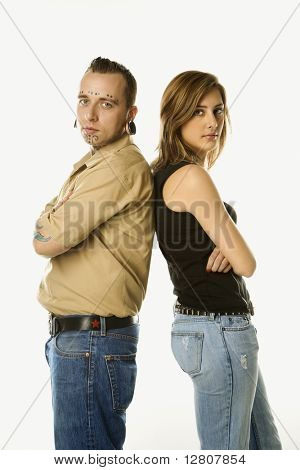 Caucasian mid-adult man and teen female standing back to back.