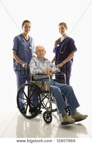 Dos hembras caucásicas usando peelings con anciano varón caucásico en silla de ruedas.