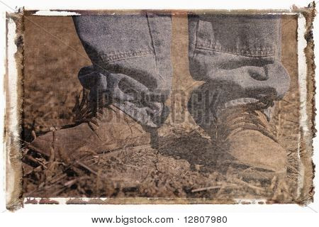 instant photo transfer of feet shot of man wearing workboots standing in soybean field.