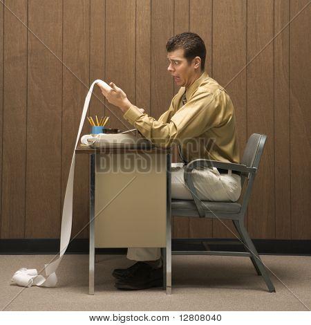 Empresário de retro Spectacles caucasion, sentado na mesa, olhando com expressão chocada em adição de longo