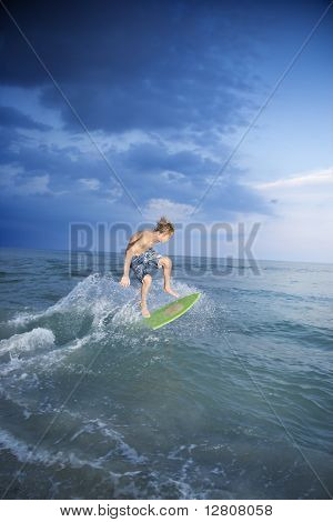 Caucasian male teen riding skimboard.