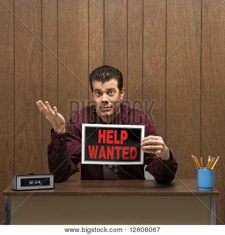 Caucasion mid-adult retro businessman sitting at desk holding help wanted sign with pleading expression.