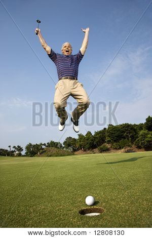 Caucasion mid-adult man holding golf club jumping in air cheering with golfball and hole in foreground.