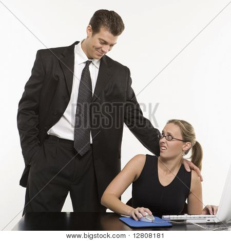 Caucasian mid-adult man sexually harassing woman sitting at computer.