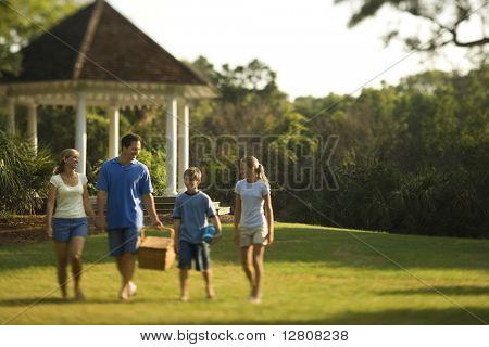 Caucasian family of four carrying picnic basket walking through park.
