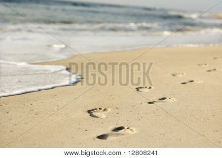 Scenic sandy coastline with footprints and waves.