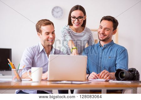I like this one. Cheerful delighted handsome guys sitting at the table while their  positive colleague standing nearby and pointing the screen of the laptop