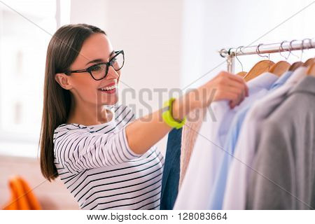 I  choose this. Pleasant overjoyed beautiful woman smiling and choosing clothes while being involved in work