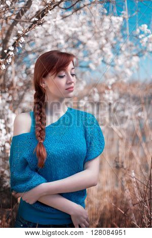 The beautiful red-haired girl stand at the blossoming apple-tree in a grass. The girl has braided a braid. The girl is dressed in an easy jacket.