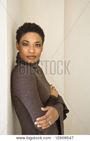 African-American woman standing leaning against wall looking at viewer.