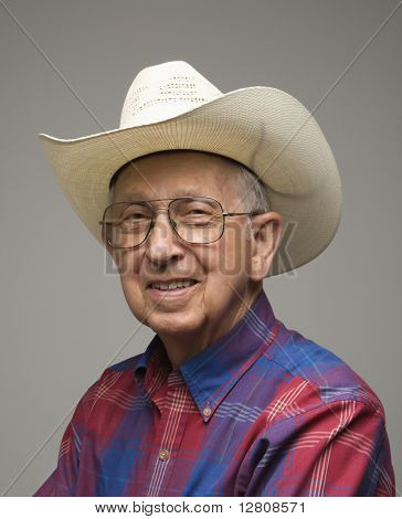 Portrait of smiling Caucasion elderly man wearing plaid shirt and cowboy hat.