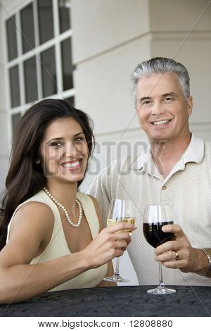 Prime adult Hispanic female and Caucasian prime adult male toasting sitting at table.