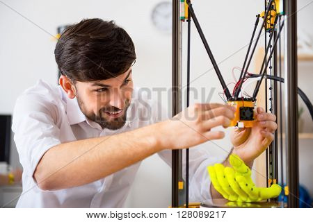 Crafty hands.   Cheerful delighted smiling man using  3d printer and expressing positivity