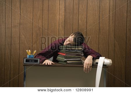 Caucasian mid-adult retro businessman sitting at desk resting his head on a tall stack of folders.