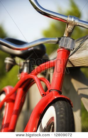 Image of red bike leaning against railing of boardwalk.