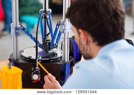 Professional approach. Pleasant man sitting at the table and working with 3d printer while being involved in work