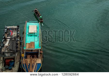 A top view shot of fishing boats over turqoise colored water.