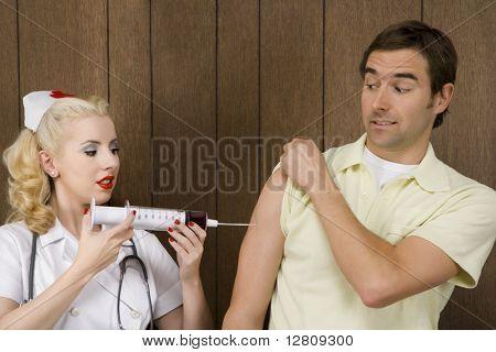 Caucasian mid-adult female nurse giving shot to man with oversized syringe.