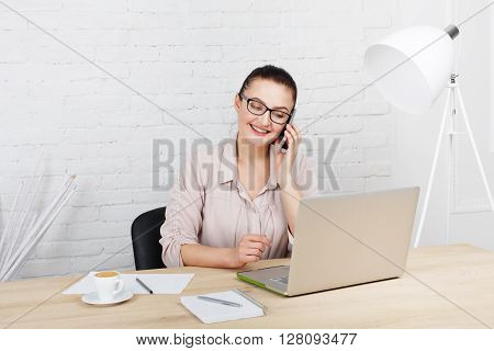 Middle aged businesswoman working in white modern office interior, with laptop and mobile cellphone. Female office work, woman in eye glasses, speaking on mobile phone. High key, soft tone.