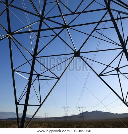 Electrical power lines in barren desert landscape.