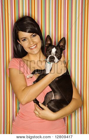 Young adult female Caucasian holding Boston Terrier dog on striped background.