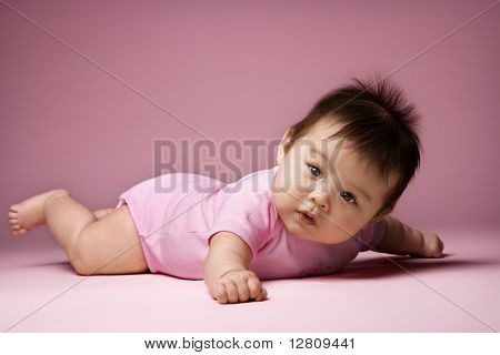 Asian baby lying on stomach looking at viewer holding arms out to side.