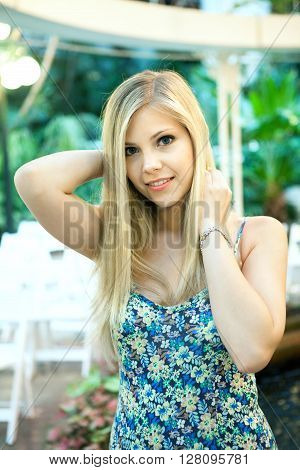 Smiling attractive blonde woman under warm tungsten lighting.