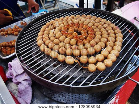 grilled Thai sausages balls on stove at market