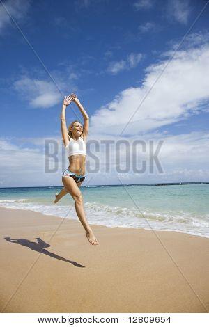 Kaukasische jonge volwassen vrouw springen op het strand.