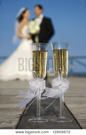 Pair of flute glasses of champagne with Caucasian bride and groom blurred in background.