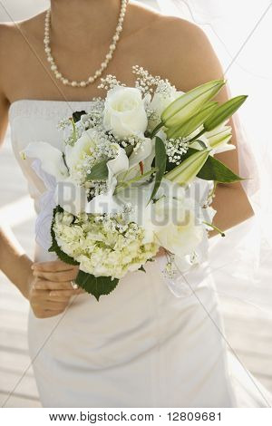 Caucasian mid-adult bride holding flower bouquet.