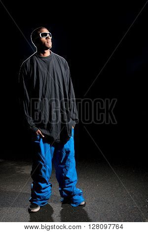 African American young man wearing baggy winter sports clothing posing under dramatic lighting with lens flare.