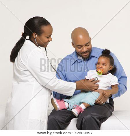 Afro-amerikanische Frau Kinderarzt untersuchen Babymädchen von Vater festgehalten.