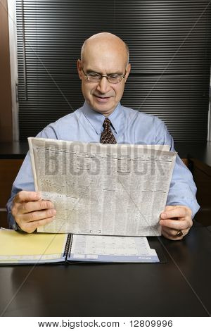 Caucasian middle-aged businessman sitting at desk in office reading newspaper smiling.