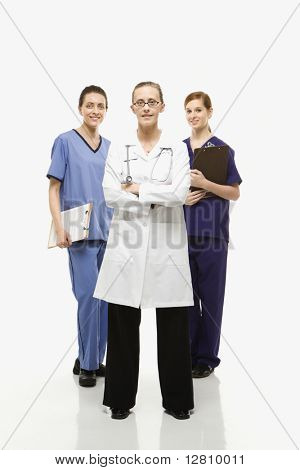 Full-length portrait of Caucasian women healthcare workers in uniforms standing against white background.