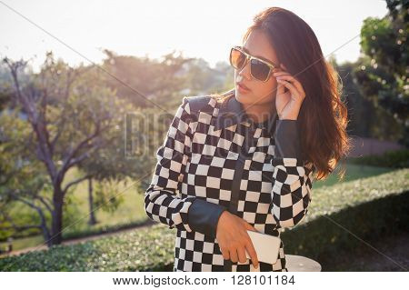 portrait of beautiful chick fashion woman wearing sun glasses and smartphone in hand against afternoon light with blur background and copy space