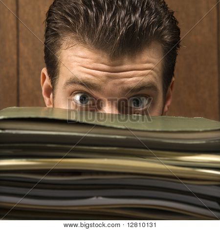 Caucasion mid-adult retro businessman peering with wide eyes over a tall stack of folders.