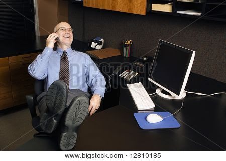 Caucasian middle-aged businessman in office sitting with feet on desk talking and laughing on cellphone.