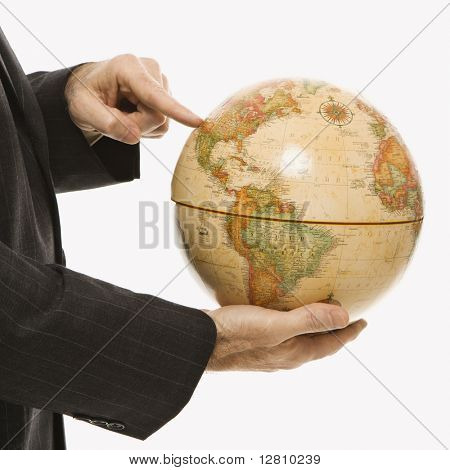 Caucasian middle-aged businessman holding globe and pointing standing in front of white background.