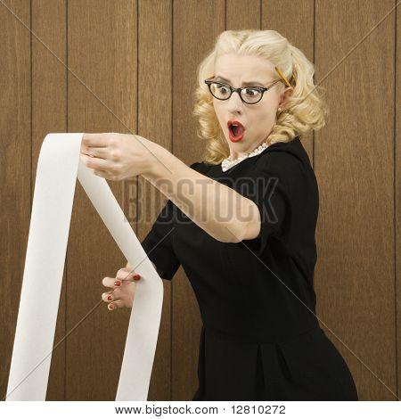 Fêmea de caucasianos Spectacles na roupa vintage, mantendo uma cópia impressa com uma expressão chocante sobre seu fa