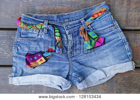 Denim shorts with scarf belt on wooden background