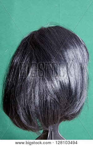 Artificial wig with black hair on a green background