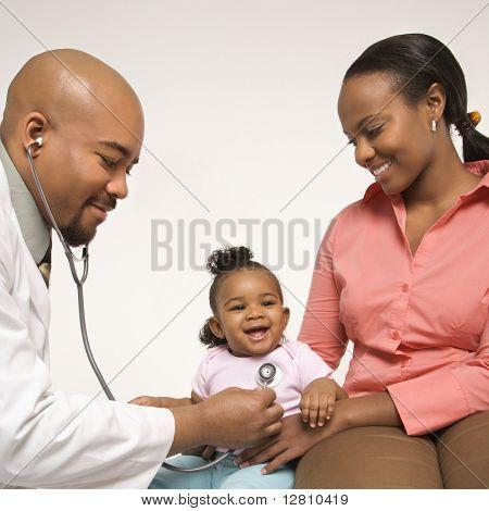 Pediatra masculino afro-americana examinando menina sendo realizada pela mãe.